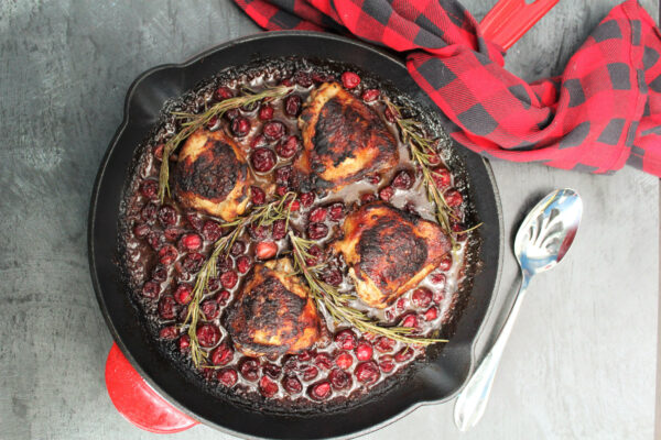 Crispy Chicken in a cast iron skillet surrounded by cranberries, rosemary and sauce